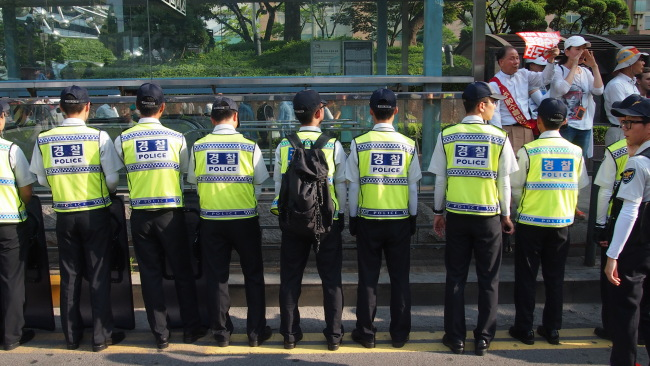 Antigay campaigners holds placards on a sidewalk, with dozens of police officers stationed in central Seoul, Sunday. (Ock Hyun-ju/The Korea Herald)