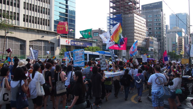 Marchers wave rainbow-colored flags at the pride parade in central Seoul, Sunday. (Ock Hyun-ju/The Korea Herald)