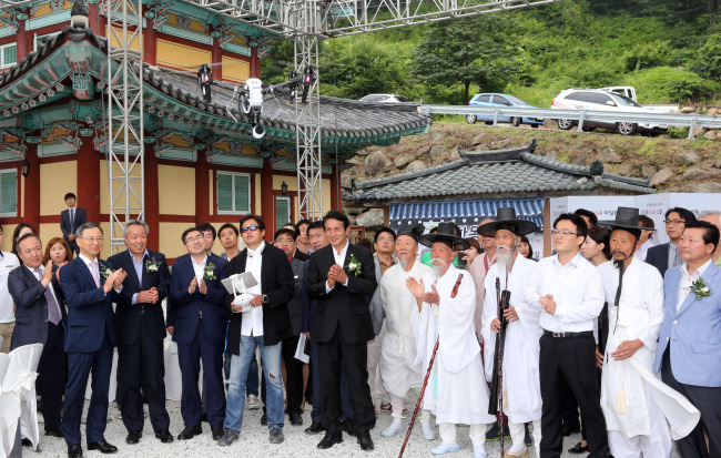 """Cheonghakdong residents and KT officials including KT chairman Hwang Chang-gyu (left, front row) watch a flying security drone during a ceremony to transform the small village into a """"GiGa Creative Town"""" on Monday. (Yonhap)"""