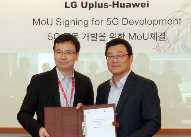 Kim Sun-tae (right), executive vice president of LG Uplus' service development division, and Yang Chao Bin, chief marketing officer of Huawei, pose at a signing ceremony of an memorandum of understanding in Shanghai on Tuesday. LG Uplus
