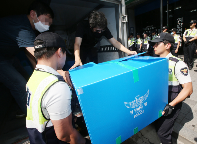Police officers carry a box containing account books, computer hard disks and other materials that they seized at the head office of Corea Alliance in Seoul, Wednesday. (Yonhap)