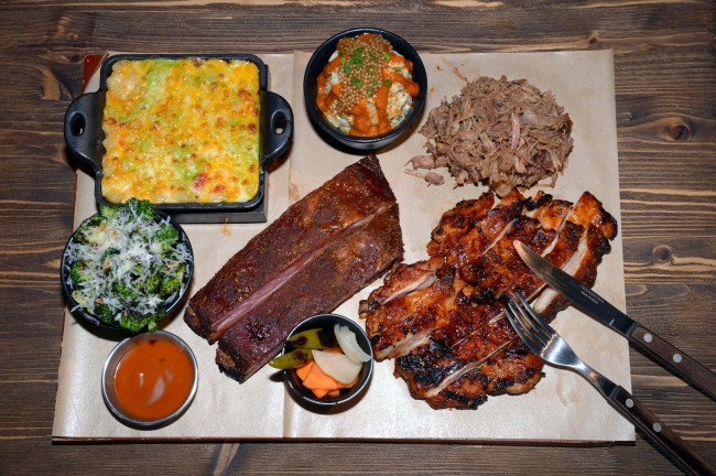 Manimal Smokehouse's pulled pork (top right), chicken (bottom right), pork spare ribs (center), chipotle lime potato salad, green chile mac and cheese, and grilled parmesan broccoli (Chung Hee-cho/The Korea Herald)