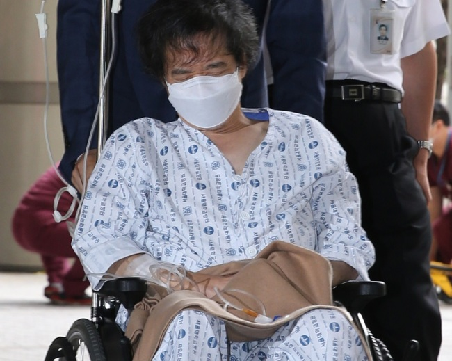 CJ chairman Lee Jay-hyun enters Seoul Appellate Court on wheel chair on Sept. 12, 2014. (Yonhap)