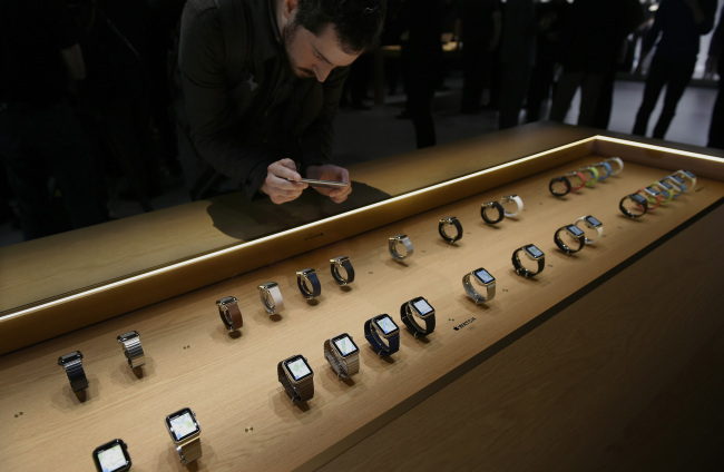 An attendee takes a photograph with an iPhone of the Apple Watches during the Apple Inc. Spring Forward event in San Francisco, California. (Bloomberg)