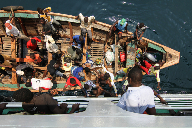 A child is handed between a small boat and the MV Liemba, which takes passengers across Lake Tanganyika between Tanzania and Zambia.(Albert Reteief)