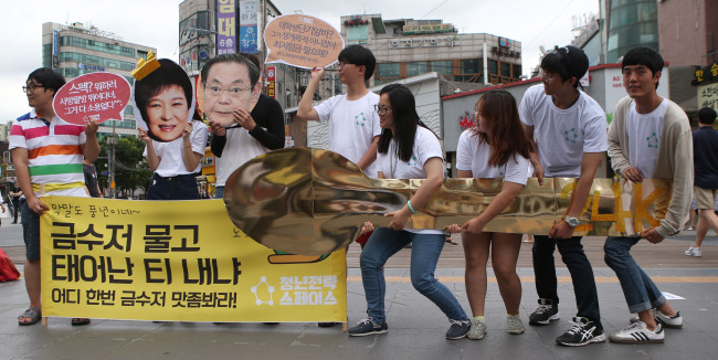 Young Koreans in Seoul protest against the government's labor policies for the nation's youth population, using a large, gold-colored spoon to criticize politicians and businessmen with prosperous backgrounds and therefore