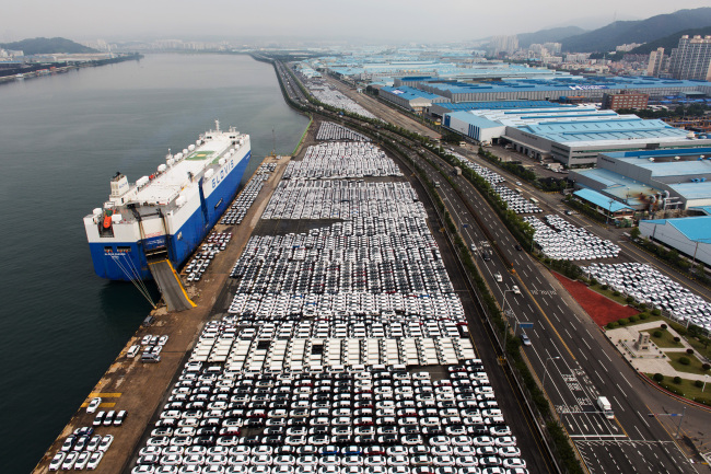 Hyundai Motor vehicles bound for export await shipment next to a cargo ship at a port near its plant in Ulsan, South Gyeongsang Province, July 21. Bloomberg