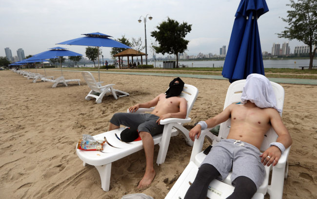 Two men in this July 2015 photo cover their faces as they lie by at the Han River bank (Yonhap)