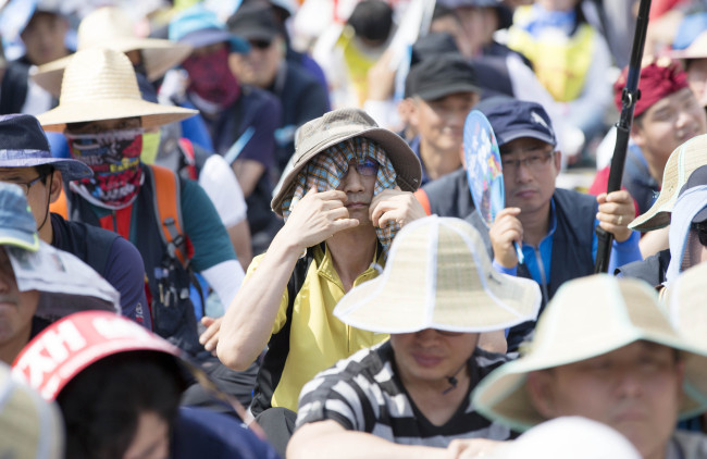 Protesters at Seoul Station Plaza shield their faces from the sun with hats and scarves last month. (Yonhap)