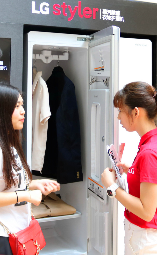 Customers look at LG Electronics` clothing care system, LG Styler, in Guangzhou, China on Thursday. (LGE)
