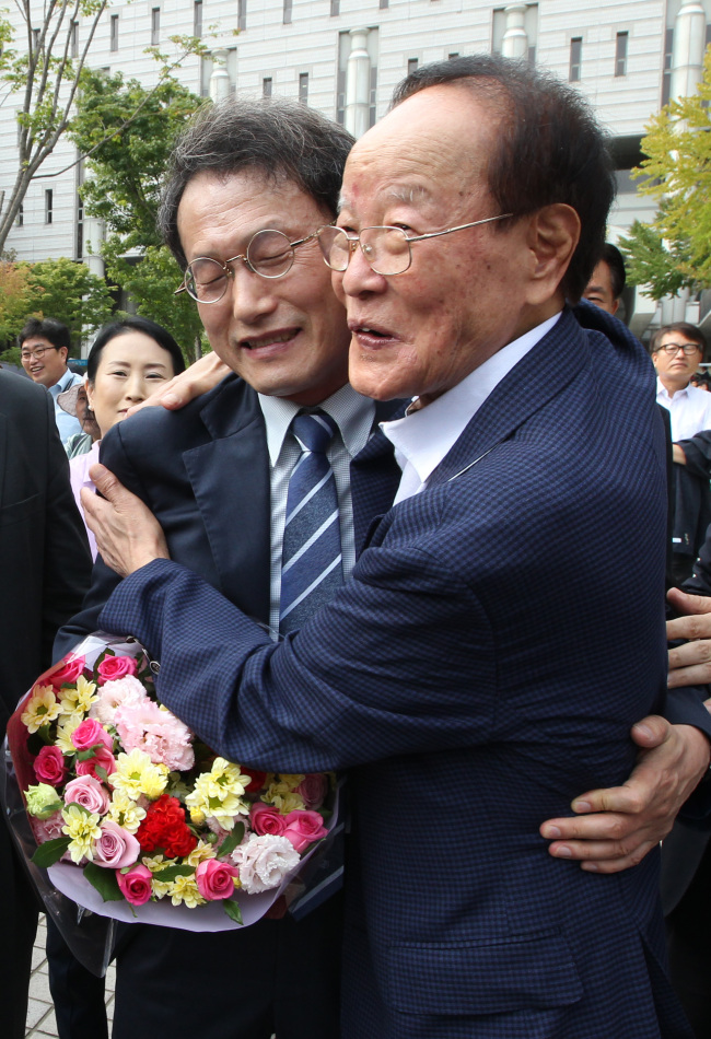 Seoul education chief Cho Hi-yeon (left) embraces his supporter outside Seoul High Court in Seocho-gu, southern Seoul. (Yonhap)