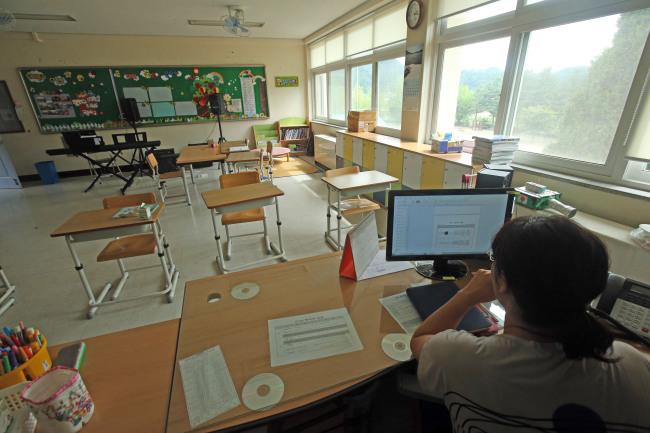 A South Korean schoolteacher is preparing for her class in an empty classroom. Yonhap