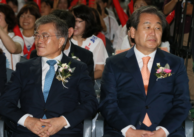 Rep. Moon Jae-in (left), the leader of the opposition New Politics Alliance for Democracy, and ruling Saenuri Party leader Rep. Kim Moo-sung sit next to each other in Jangchoong Stadium in Seoul on Wednesday. (Yonhap)