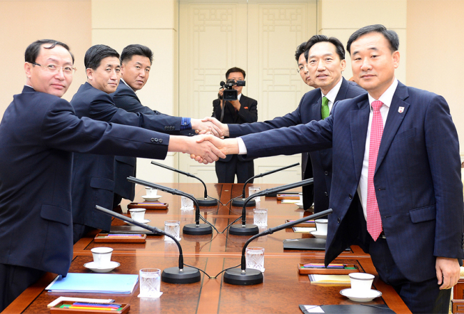 South Korean and North Korean officials shake hands at the talks on family reunions at the truce villiage of Panmunjom, Monday. (Yonhap)