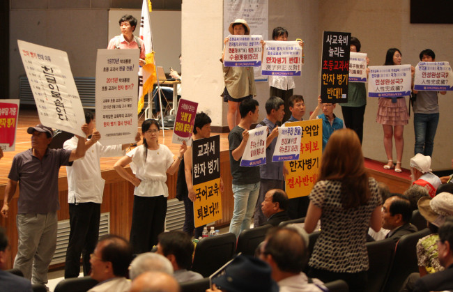 Members of civic groups opposing the use of Chinese characters in elementary school textbooks hold up placards during the Education Ministry's public hearing held at Korea National University of Education in Cheongju, North Chungcheong Province, on Aug. 24. (Yonhap)