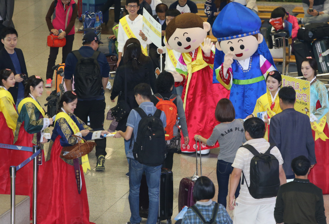 Korea Tourism Organization officials welcome Chinese tourists arriving in Seoul for China's National Day holiday Friday at Incheon International Airport. (Yonhap)