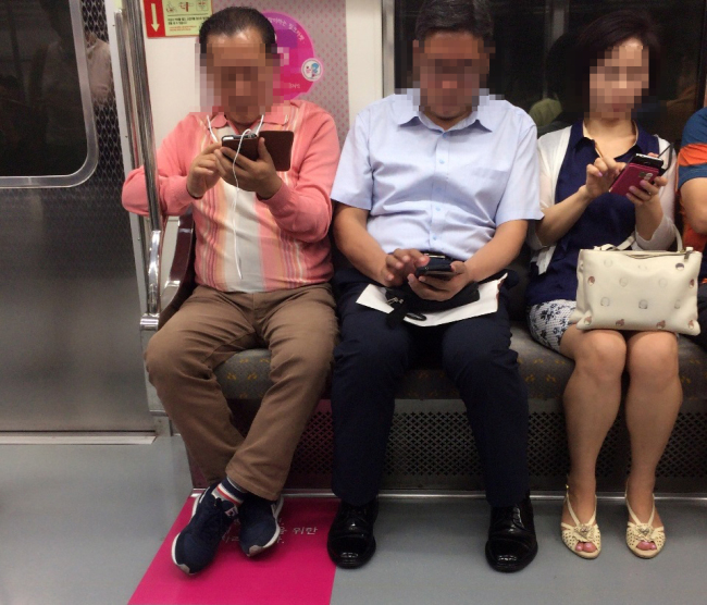 A priority seat designated for pregnant women (marked in pink) is occupied by a non-pregnant passenger in a Seoul subway train. (Claire Lee/The Korea Herald)