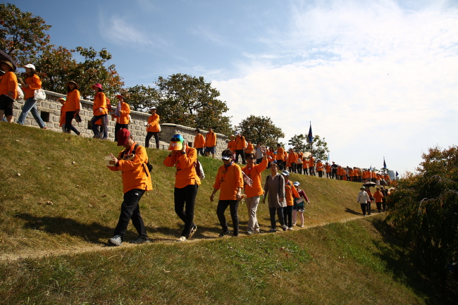Tourists in traditional straw shoes stroll around Hwaseong Fortress.