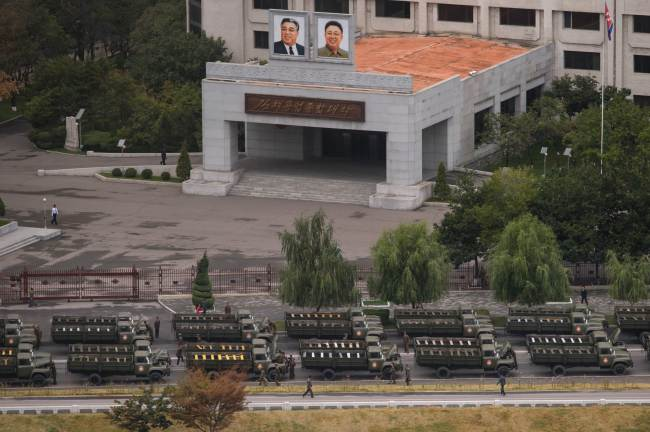 Empty military vehicles line up on a road before a building displaying portraits of late North Korean leaders Kim Il-Sung (top left) and Kim Jong-Il (top right) in Pyongyang, Saturday. North Korea is gearing up for a lavish celebration marking the 70th anniversary of its ruling Workers` Party. (AFP-Yonhap)
