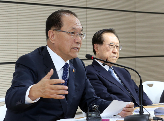 Education Minister Hwang Woo-yea (left) answers questions during a policy briefing Monday about government plans to revive state history textbooks for secondary education at the Sejong Government Complex. (Yonhap)