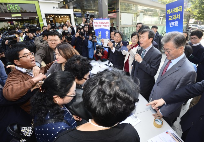 Members of a conservative civic group protest against NPAD chairman Rep. Moon Jae-in (right) and other party members who were holding a rally opposing the government's revival of state-published history textbooks in Yeouido, Tuesday. (Yonhap)