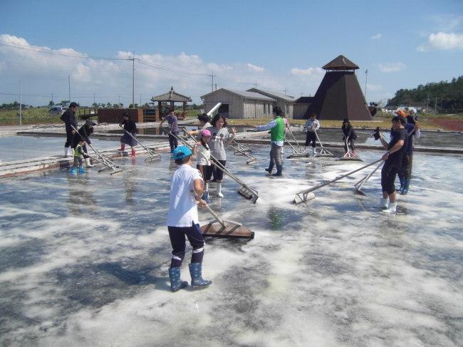 Tourists participate in a program to learn how to make salt at a farm on Jeungdo Island. (Park Hyong-ki/The Korea Herald)