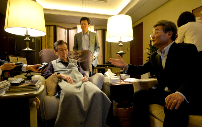 Lotte Group founder and general chairman Shin Kyuk-ho (left) and his eldest son Shin Dong-joo (second from left) speak with reporters inside the general chairman's office in Lotte Hotel Seoul on Friday. (Yonhap)
