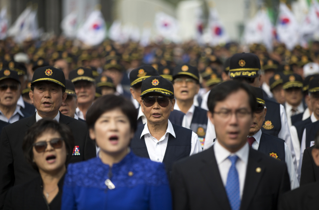 """Participants of a rally decrying the """"political bias"""" of current history textbooks including ruling Saenuri Party officials sing the national anthem Thursday at Seoul Station in Yongsan-gu, Seoul. (Yonhap)"""