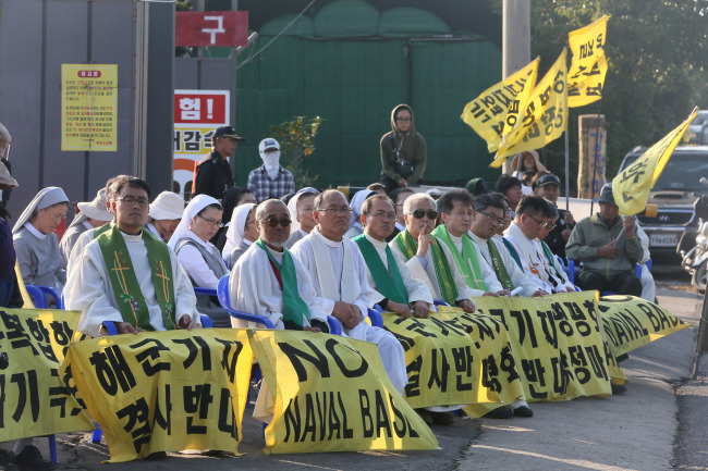 Priests hold Mass in front of the construction site on Jejudo Island on Oct. 12 in protest against the anticipated launch of a naval base. (Yonhap)