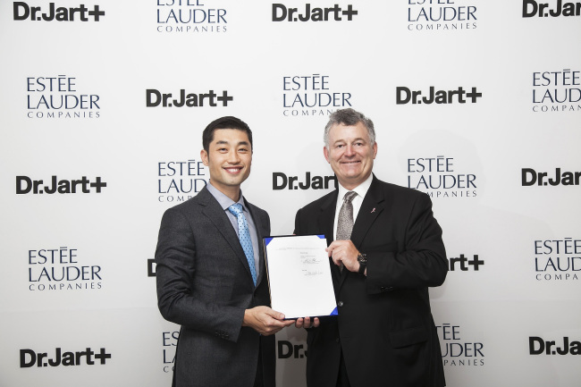 The Estee Lauder Companies executive chairman William P. Lauder (right) signs an investment deal with Dr. Jart+ CEO Lee Jin-wook in New York on Sunday. (The Estee Lauder Companies / Dr. Jart+)