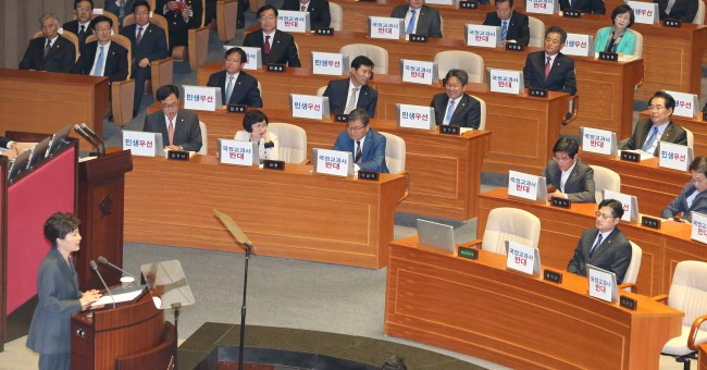 Theopposition members sit with their laptops holding up signs denouncing her textbook plan while Park delivers her speech. (Yonhap)