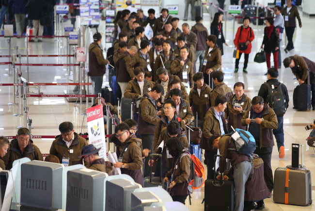 South Korea`s labor union members wait in line at an airport to attend a freindly soccer match in Pyongyang. Yonhap