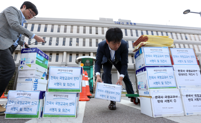 Education Ministry officials move boxes containing petitions gathered and sent by the main opposition New Politics Alliance for Democracy opposing the government's reinstatement of state-authored history textbooks in front of the ministry building in Sejong City on Monday. (Yonhap)