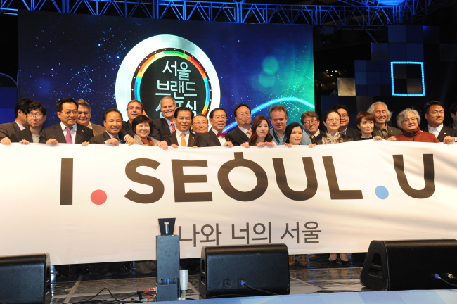 """Seoul City Mayor Park Won-soon (center) and guests hold up a placard with the city's new brand, """"I.SEOUL.U,"""" at a ceremony held at Seoul Plaza on Oct. 28. (Yonhap)"""