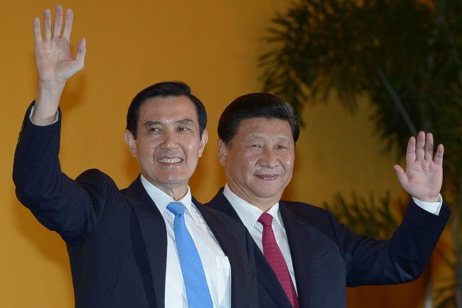 Chinese President Xi Jinping and Taiwan President Ma Ying-jeou wave to members of the media at the Shangri-la Hotel in Singapore on Saturday. AFP-Yonhap