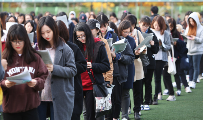 Students taking the annual college entrance exam to be held Thursday line up to receive instructions for the exam at Suwon High School for Agricultural Science in Suwon, Gyeonggi Province, Wednesday. Yonhap