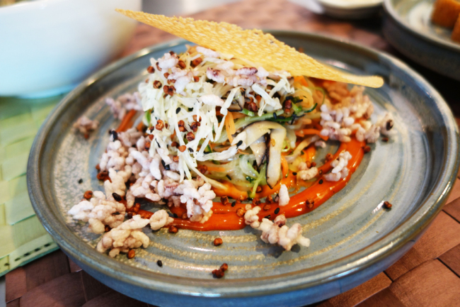 Salad bibimbap, made with vitamin E-enriched black rice, vegetables, a gochujang (red chili paste) and mayonnaise sauce, and a crispy, fried buckwheat top (Rumy Doo/The Korea Herald)