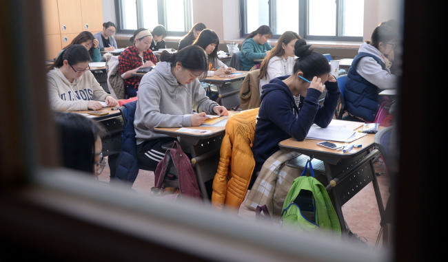 Students get a last-minute read before the college entrance exam at a school in Seoul on Thursday. ( Park Hyun-koo/The Korea Herald)