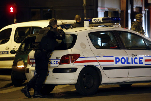 Police officers secure the area near La Belle Equipe, rue de Charonne, at the site of an attack on Paris on November 14, 2015 after a series of gun attacks occurred across Paris as well as explosions outside the national stadium where France was hosting Germany. More than 100 people were killed in a mass hostage-taking at a Paris concert hall and many more were feared dead in a series of bombings and shootings, as France declared a national state of emergency. (AFP)