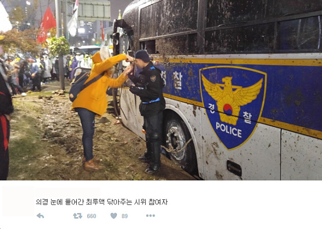 A citizen washes tear gas from the face of a conscripted policeman during a mass rally in Gwanghwamun, Seoul, Saturday. The picture posted on Twitter has been shared among numerous social media and online communities. (Twitter)