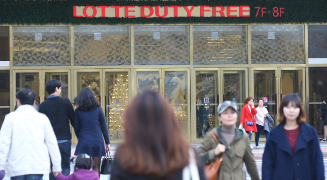 People walk past the Lotte Duty Free store at Lotte World Tower in Gangnam, Seoul. (Yonhap)