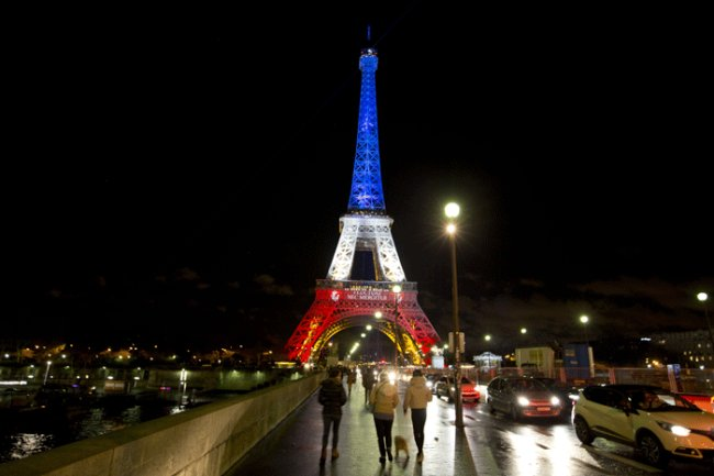 People walk towards the illuminated Eiffel Tower in the French national colors red, white and blue in honor of the victims of the attacks last Friday in Paris, Nov. 17 (Yonhap-AP)