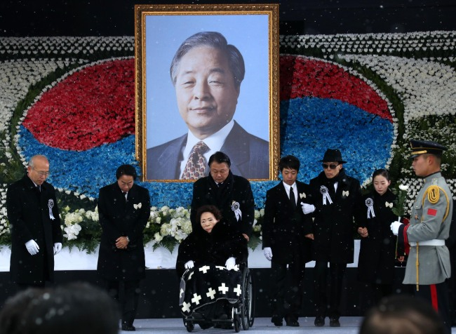 Bereaved family members of late former President Kim Young-sam, including former first lady Son Myung-soon (in the wheelchair), return after offering flowers Thursday at a state funeral held at the National Assembly. (Yonhap)