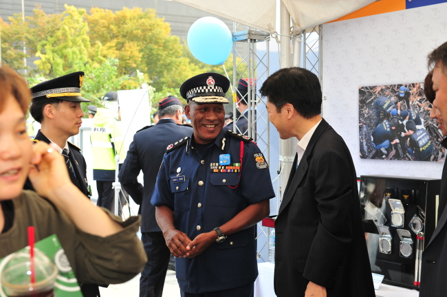 Gari L. Baki, police chief of Papua New Guinea, talks to a Korean police official at an outdoor exhibition held to commemorate the 70th anniversary of the Korean police on Oct. 21, at Gwanghwamun Square, central Seoul. (KNPA)