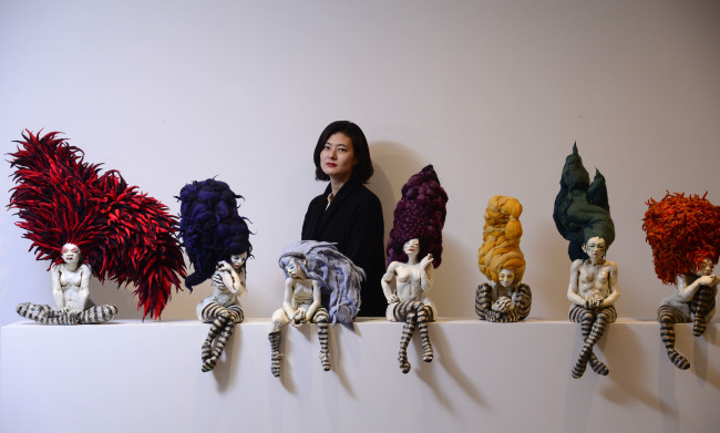 "Artist Sohn Jung-hee stands behind the ""Debutantes: 7 Sins"" series displayed at Hakgojae Gallery in Seoul, Dec. 4.(Park Hae-mook/The Korea Herald)"