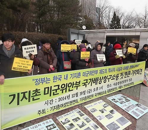 Activists hold signs in front of the Seoul Central District Court, where the press conference calling for the comfort women's right to claim damages was held on Dec. 19, 2014. Yonhap