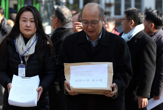 Professors and lawyers opposing the state-authored history textbooks head into the Constitutional Court in Seoul to hand in their appeal on Tuesday. (Yonhap)