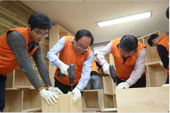 Hanwha E&C CEO Choi Kwang-ho (second from left) helps make bookshelves during the builder's social contribution program to donate a library for the disabled on Wednesday. Hanwha E&C
