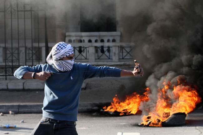 A Palestinian protester uses a slingshot to throw stones during clashes with Israeli security forces at the main entrance of the West Bank city of Bethlehem on Friday. New violence erupted in the West Bank the day before with four Palestinian attackers shot dead by Israeli forces, as Israel recoiled over a video showing Jewish extremists celebrating a Palestinian toddler`s death. (AFP-Yonhap)