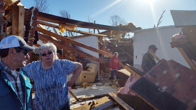 Charles and Daisy Johnson, of Benton County, Miss., left, survey the damage to their home, Thursday. The couple were temporarily trapped in their shelter Wednesday as a severe winter storm rolled over their home. At least seven people were killed in Mississippi, Tennessee and Arkansas as spring-like storms mixed with unseasonably warm weather rolled through the South. (AP-Yonhap)